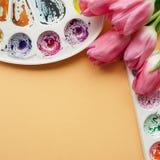Endecha creativa del plano de las paletas de la acuarela y del ramo de tulipanes rosados Lugar de trabajo del artista en un fondo Imagen de archivo libre de regalías