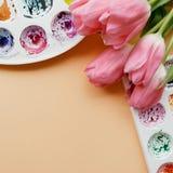 Endecha creativa del plano de las paletas de la acuarela y del ramo de tulipanes rosados Lugar de trabajo del artista en un fondo Fotos de archivo libres de regalías