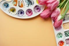 Endecha creativa del plano de las paletas de la acuarela y del ramo de tulipanes rosados Lugar de trabajo del artista en un fondo Fotografía de archivo