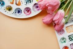 Endecha creativa del plano de las paletas de la acuarela y del ramo de tulipanes rosados Lugar de trabajo del artista en un fondo Fotografía de archivo libre de regalías