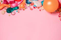 Endecha del plano de la celebración Caramelo con los artículos coloridos del partido en vagos rosados imagen de archivo