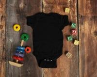 Endecha del plano de la maqueta de la camisa negra del mono del bebé fotos de archivo libres de regalías