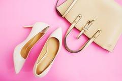 Endecha femenina del plano de los accesorios Zapatos y bolso de la mujer en fondo rosado Accesorios beige de la mujer del color E Imagenes de archivo