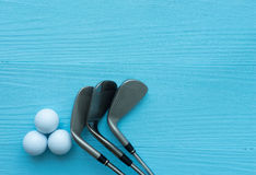 Endecha plana: Clubs de golf, pelotas de golf en la tabla de madera azul Imagenes de archivo