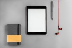 Endecha plana con el iPad y el cuaderno rojos de los auriculares Fotos de archivo libres de regalías