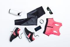 Endecha plana con la ropa de deportes, la botella de agua juguetona para entrenar y los dispositivos digitales Imagenes de archivo