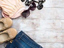 Endecha plana con la ropa del ` s de la mujer, zapatos de los vidrios Foto de archivo libre de regalías