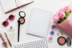 Endecha plana con la tableta digital, los diversos cosméticos, los accesorios y el ramo de tulipanes rosados Fotos de archivo libres de regalías