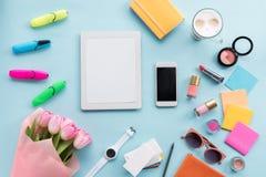 Endecha plana con la tableta, el smartphone, los diversos accesorios y las flores Imagen de archivo libre de regalías