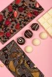 Endecha plana con las barras de chocolate clasificadas con las frutas y nueces y caramelos Fotografía de archivo libre de regalías