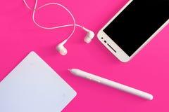 Endecha plana con los dispositivos modernos, tableta digital, smartphone, pluma en fondo del color Fotos de archivo