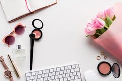 Endecha plana con los diversos cosméticos, accesorios y ramo de tulipanes rosados Imágenes de archivo libres de regalías