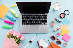 Endecha plana con los diversos cosméticos, el ramo de flores, los accesorios y el ordenador portátil Fotografía de archivo libre de regalías