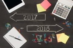 endecha plana con los materiales de oficina, flechas con 2017 y 2018 números Imagen de archivo