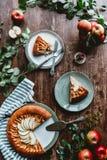 endecha plana con los pedazos de empanada de manzana en las placas, los cubiertos, el lino, las hojas del verde y las manzanas fr imagenes de archivo