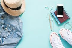 Endecha plana de artículos turísticos con el dispositivo móvil, el pasaporte y la ropa en color en colores pastel Imagen de archivo libre de regalías