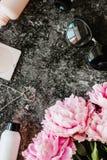 Endecha plana de la belleza con los accesorios, el perfume, los cosméticos y las peonías en un fondo de mármol oscuro Imagenes de archivo
