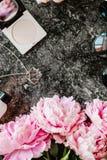 Endecha plana de la belleza con los accesorios, el perfume, los cosméticos y las peonías en un fondo de mármol oscuro Imagen de archivo libre de regalías
