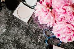 Endecha plana de la belleza con los accesorios, el perfume, los cosméticos y las peonías en un fondo de mármol oscuro Fotografía de archivo