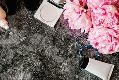 Endecha plana de la belleza con los accesorios, el perfume, los cosméticos y las peonías en un fondo de mármol oscuro Fotos de archivo