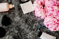 Endecha plana de la belleza con los accesorios, el perfume, los cosméticos y las peonías en un fondo de mármol oscuro Fotos de archivo libres de regalías