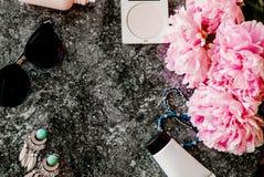 Endecha plana de la belleza con los accesorios, el perfume, los cosméticos y las peonías en un fondo de mármol oscuro Foto de archivo