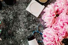 Endecha plana de la belleza con los accesorios, el perfume, los cosméticos y las peonías en un fondo de mármol oscuro Fotografía de archivo libre de regalías