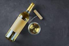 Endecha plana de la botella de mentira del vino blanco con la etiqueta, el sacacorchos y el vidrio vacíos para probar imagenes de archivo