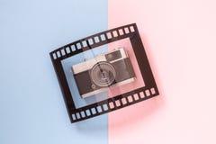 Endecha plana de la cámara y del bastidor del vintage en forma de película análoga en concepto minimalistic del fondo multicolor Foto de archivo libre de regalías