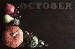 Endecha plana de la caída rústica hermosa con las hojas, las calabazas, las castañas y las letras octubre en fondo de madera imagen de archivo