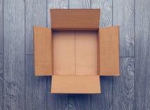 Endecha plana de la caja abierta vacía en superficie de madera Imágenes de archivo libres de regalías