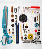 Endecha plana de la herramienta y de accesorios de costura en el backgrou de madera blanco Foto de archivo libre de regalías