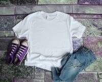 Endecha plana de la maqueta blanca de la camiseta en fondo púrpura del ladrillo con la PU fotos de archivo libres de regalías