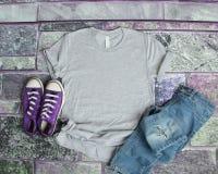 Endecha plana de la maqueta gris de la camiseta en fondo púrpura del ladrillo con el pur imagenes de archivo