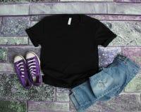Endecha plana de la maqueta negra de la camiseta en fondo púrpura del ladrillo con la PU fotos de archivo libres de regalías