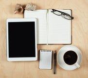 Endecha plana de la tableta, del cuaderno, de la taza de café y del lápiz con el centro en blanco en el fondo de madera, visión s Foto de archivo libre de regalías