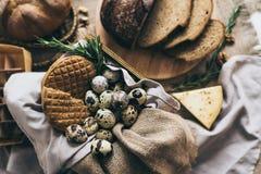 Endecha plana de las rebanadas de la torta del pan con los huevos de codornices, hierbas, queso Taza amarilla de leche Servilleta Fotografía de archivo