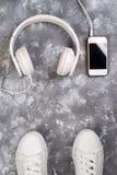 Endecha plana de las zapatillas de deporte blancas en el fondo de piedra con el teléfono y los auriculares Fotos de archivo libres de regalías
