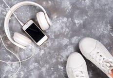 Endecha plana de las zapatillas de deporte blancas en el fondo de piedra con el teléfono y los auriculares Fotografía de archivo