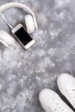 Endecha plana de las zapatillas de deporte blancas en el fondo de piedra con el teléfono y los auriculares Imágenes de archivo libres de regalías