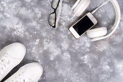 Endecha plana de las zapatillas de deporte blancas en el fondo de piedra con el teléfono y los auriculares Fotografía de archivo libre de regalías