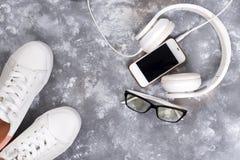 Endecha plana de las zapatillas de deporte blancas en el fondo de piedra con el teléfono y los auriculares Fotos de archivo