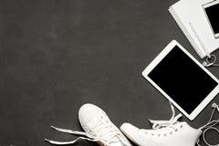 Endecha plana de las zapatillas de deporte blancas en fondo negro con el teléfono, auriculares, tableta, libro de la copia Imagen de archivo