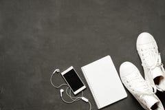Endecha plana de las zapatillas de deporte blancas en fondo negro con el teléfono, auriculares, tableta, libro de la copia Fotografía de archivo libre de regalías