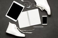 Endecha plana de las zapatillas de deporte blancas en fondo negro con el teléfono, auriculares, tableta, libro de la copia Fotos de archivo libres de regalías