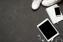 Endecha plana de las zapatillas de deporte blancas en fondo negro con el teléfono, auriculares, tableta, libro de la copia Foto de archivo libre de regalías