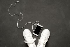 Endecha plana de las zapatillas de deporte blancas en fondo negro con el teléfono y los auriculares Fotografía de archivo