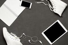 Endecha plana de las zapatillas de deporte blancas de la moda en fondo negro con el teléfono, auriculares, tableta, libro de la c Imagen de archivo libre de regalías