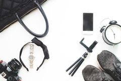 Endecha plana de los accesorios de la mujer con el teléfono móvil y de los artículos negros del color en el fondo blanco Foto de archivo