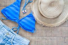 Endecha plana de los artículos de la playa del verano para la mujer en la madera Foto de archivo